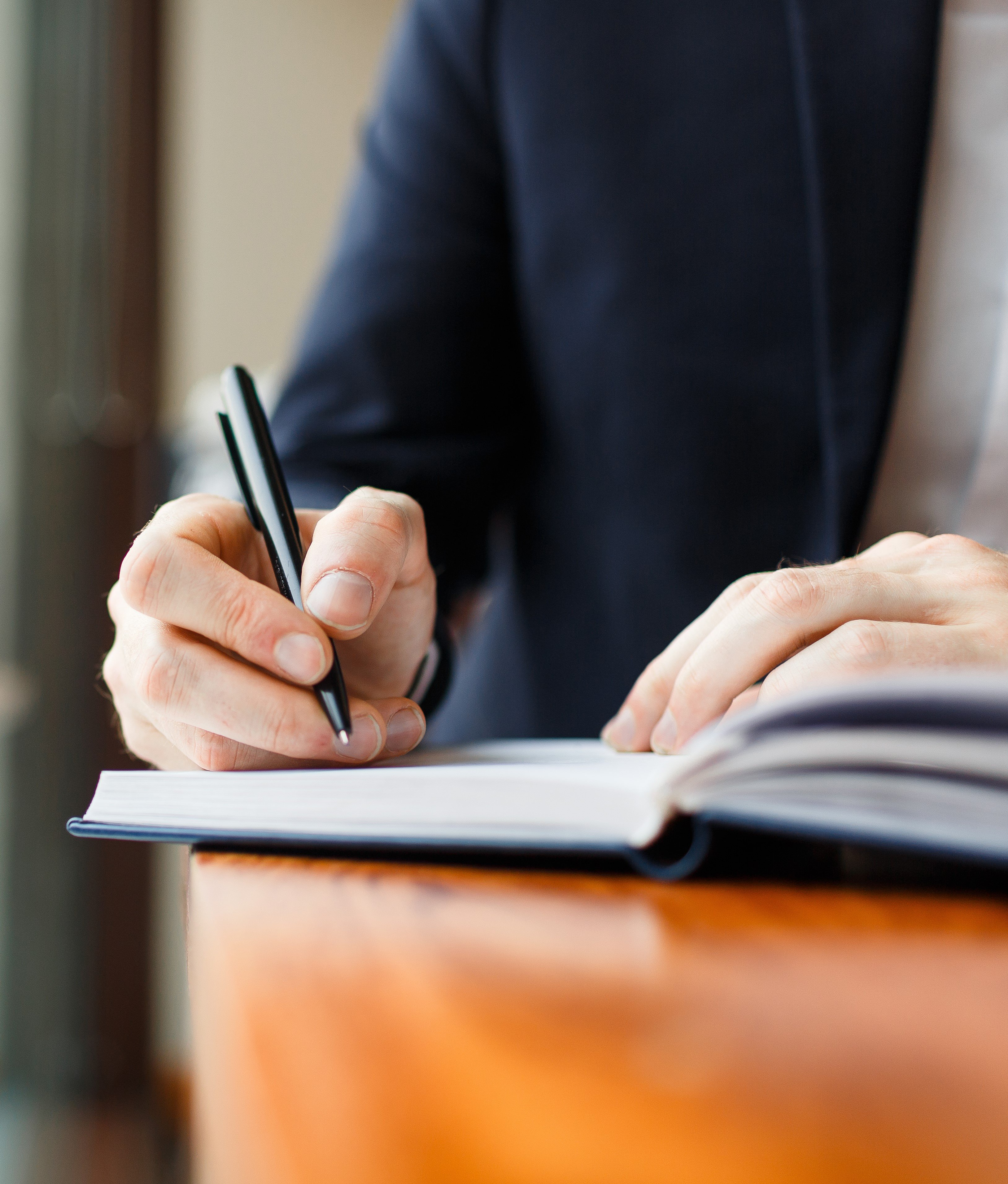 Man's hand writing in a notebook