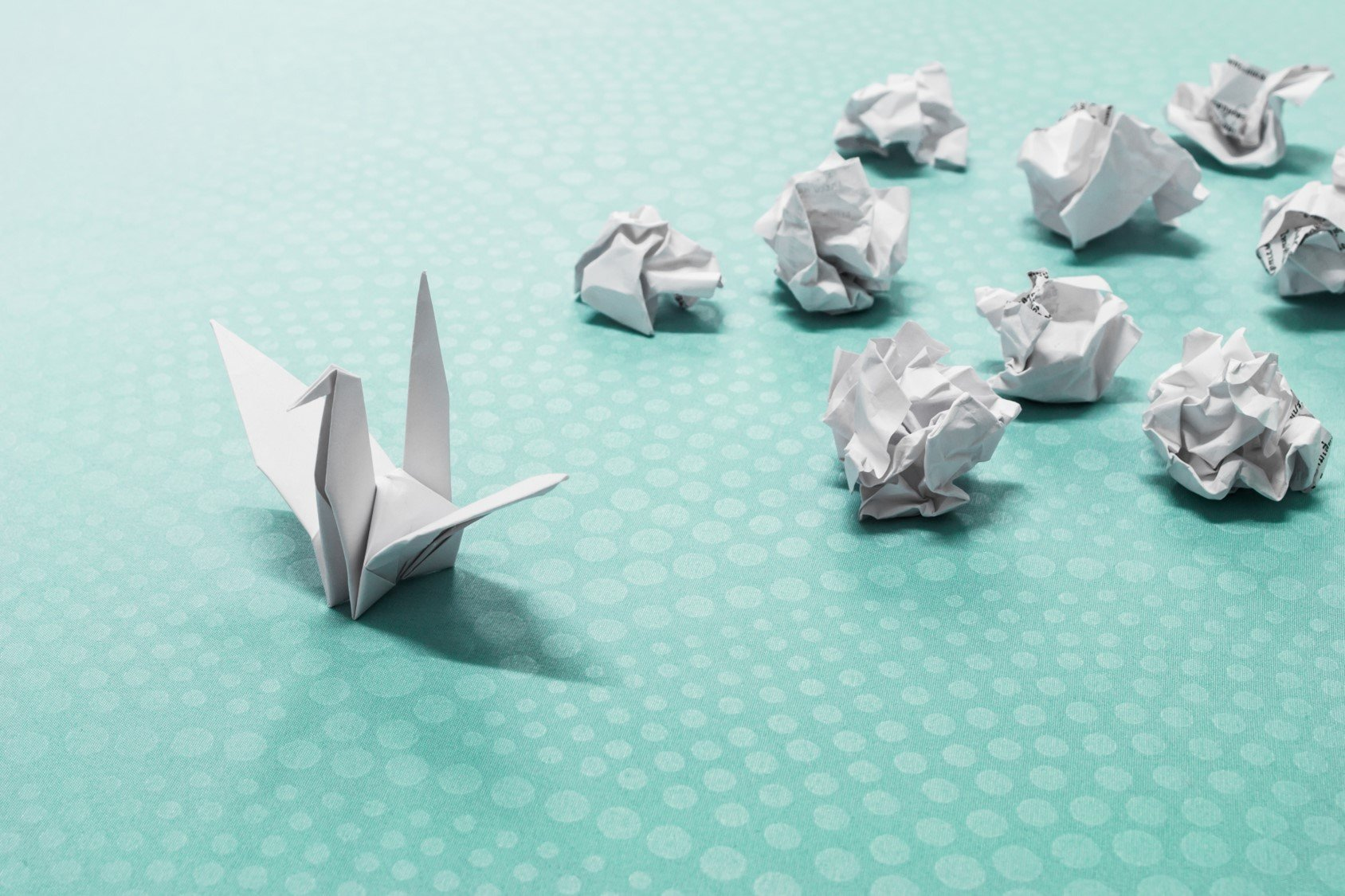 An origami swan leading a pack of screwed up balls of paper